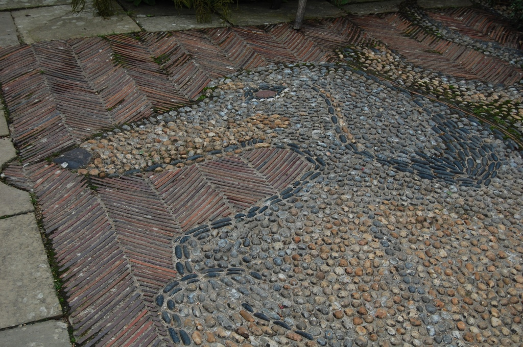 A mosaic portrait of one of Christopher Lloyd's dachsunds set into the paving.