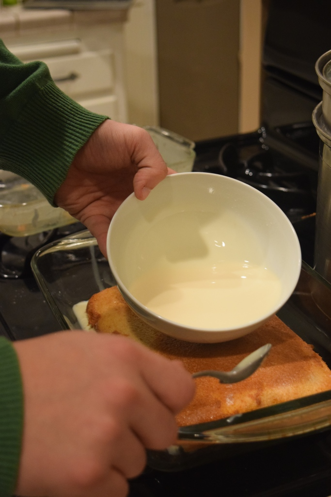 The tres leches being poured onto the cake.