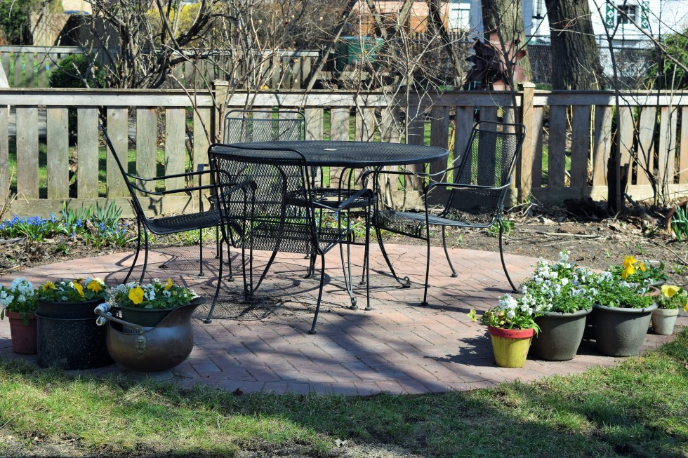 Patio in the back garden with flowering containers.