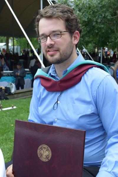 Daniel holding his diploma.